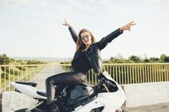 Cieszący się moment kobiety rowerzysty pozuje z rękami up obsiadanie na mo Obraz Stock