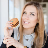 Cieszyć się hamburger: jedzący wyśmienicie hamburgeru pięknej młodej kobiety ma zabawę w restauraci lub sklep z kawą szczęśliwym  Obrazy Royalty Free