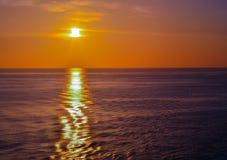 Cieux oranges avec Sun plaçant au-dessus de l'océan Photo stock