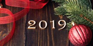 Cifre di legno scolpite che formano numero 2019 su fondo di legno immagini stock