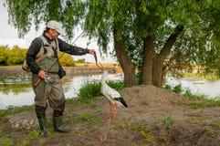 Cigüeña y pescador Fotografía de archivo