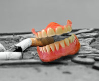 Cig butt in false teeth. Photo of cigarette butt stuck in set of false teeth in ashtray.background ideal for text etc Royalty Free Stock Images