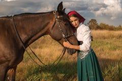 Cigano com um cavalo no campo no verão imagem de stock