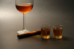 Cigar and alcohol. On dark background Royalty Free Stock Image