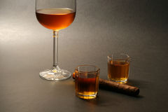 Cigar and alcohol. Cigar with wine and liquour on dark background Royalty Free Stock Photography