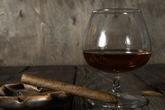 The cigar in the ashtray and a glass of cognac on oak textured table. Copy past Royalty Free Stock Images