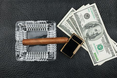 Cigar, ashtray, lighter, money on genuine leather Stock Photo