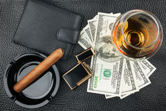 Cigar, ashtray, lighter, money, purse, glass   on genuine leathe Royalty Free Stock Photography