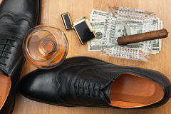 Cigar, ashtray, lighter, money, shoe, glass   on  wooden floor Royalty Free Stock Images