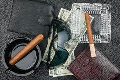 Cigar, ashtray, sunglasses, money, purse, on genuine leather Royalty Free Stock Photos
