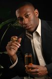 Cigar Bar. A handsome man in a cigar bar with a glass of wine Royalty Free Stock Photo