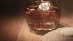 Cigar being placed beside tumbler of whiskey on the rocks Stock Photo