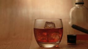 Cigar being smoked beside tumbler of whiskey on the rocks Stock Images