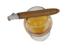 Cigar and brandy. Cigar with white ashes on a sniffer glass with brandy. Isolated on a white background Royalty Free Stock Images