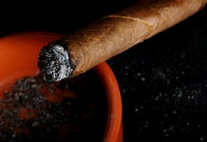 A cigar burning in the ash tray Stock Photos