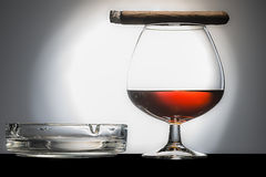 Cigar and cognac. With ashtray on a black shelf Royalty Free Stock Photo