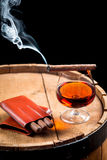 Cigar and cognac on black background with old barrel Stock Photography