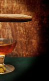 Cigar on the glass with alcohol on green felt Royalty Free Stock Photos