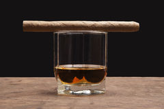 Cigar and glass of whiskey. On a dark background Royalty Free Stock Image