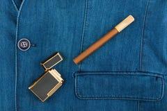 Cigar and lighter lying on a blue denim jacket Stock Images