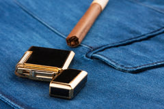 Cigar and lighter lying on a blue denim jacket Royalty Free Stock Images