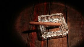 Cigar lying in an ashtray on an old wooden table in a ray of light. Panorama.
