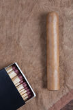 Cigar and matches. Cigar and matches on a brown background Royalty Free Stock Images