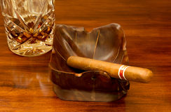 Cigar and Rum. A little taste of Cuba. Cigar in wood ashtray and rum in cut crystal glass Royalty Free Stock Photography