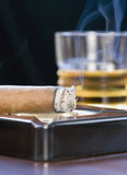 Cigar with scotch. A smoking cigar resting in ashtray, and a glass of scotch (neat) softly blurred in background stock images