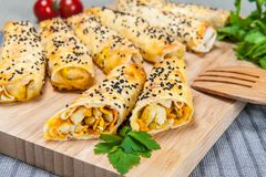 Cigar shaped bakery roll with chicken and vegetables on wood board stock image