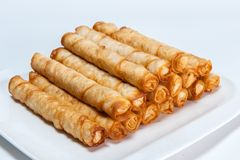 Cigar shaped bakery on white plate stock photos