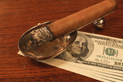 Cigar on a stand with money Royalty Free Stock Photo