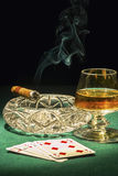 Cigar switched on. cards and the drink in the glass. The cigar switched on, and the glass with alcohol and playing cards Stock Photography