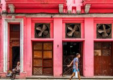 Cigar vendor  in front of pink house in Havana. Young guy passing by cigar street vendor in Havana Royalty Free Stock Images