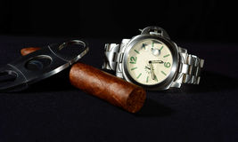 Cigar and watch with black background Stock Photos