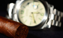 Cigar and watch with black background Royalty Free Stock Image
