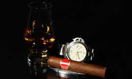 Cigar and watch whit black background Royalty Free Stock Photos