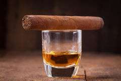 Cigar and whisky on old wooden table Royalty Free Stock Photo