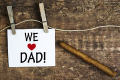 Cigar and white sign with the words We Love Dad Royalty Free Stock Photos