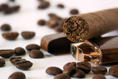 Cigare sur des grains de café proches plus légers image libre de droits