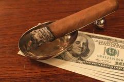 Cigare sur un stand avec de l'argent Photo libre de droits