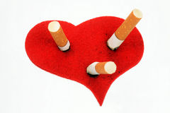 Cigaret butts in heart. On a white background Royalty Free Stock Photos