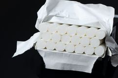 Cigarets box. Lot of white cigarets in paper box  on black background Stock Photography