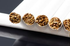 Cigarets box. Lot of white cigarets in paper box  on black background Royalty Free Stock Photos