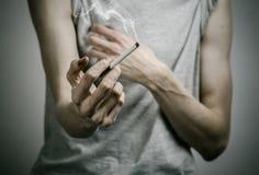 Cigarett-, böjelse- och allmän hälsaämne: rökaren rymmer cigaretten i hans hand och en röd hjärta på en mörk bakgrund i arkivfoton