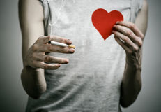 Cigarett-, böjelse- och allmän hälsaämne: rökaren rymmer cigaretten i hans hand och en röd hjärta på en mörk bakgrund i Arkivfoto