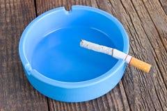 Cigarett i askfat på träbakgrund royaltyfri foto