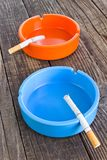 Cigarett i askfat på träbakgrund arkivfoto
