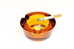 Cigarett i ett glass askfat Arkivfoton