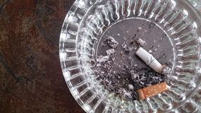 Cigarett i exponeringsglas på den wood tabellen och bakgrunder Royaltyfri Bild
